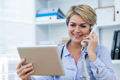 Doctor talking on telephone while using digital tablet. In clinic Stock Image