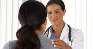 Doctor talking to African American patient using pad Stock Image