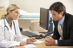 Doctor talking to businessman patient Stock Photos