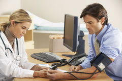 Doctor talking to businessman patient Royalty Free Stock Images