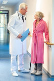 Doctor talking to an elderly woman in the corridor. Royalty Free Stock Photography
