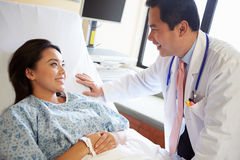 Doctor Talking To Female Patient On Ward Royalty Free Stock Image