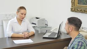 Doctor talking to her male patient at office.  stock footage