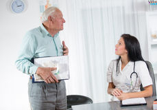 Doctor talking to her male senior patient at office Stock Photos