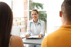 Doctor talking to her patients. In hospital stock photos