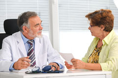 Doctor talking to his female patient Stock Image