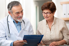 Doctor talking to his female senior patient Royalty Free Stock Photos