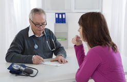 Doctor talking to his female young  patient at the office Royalty Free Stock Photo