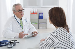 Doctor talking to his female young  patient at the office Royalty Free Stock Image