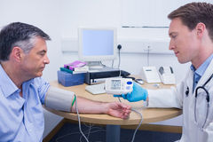 Doctor talking to his patient about his blood pressure Stock Images