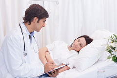 Doctor talking to his patient that just woke up Royalty Free Stock Images