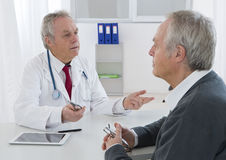 Doctor talking to his senior patient at the office Royalty Free Stock Photos