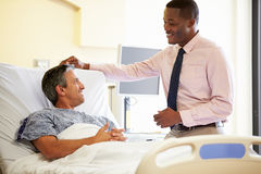 Doctor Talking To Male Patient In Hospital Room Stock Photos