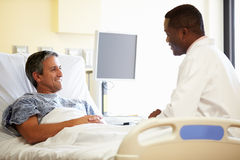 Doctor Talking To Male Patient In Hospital Room Stock Photo