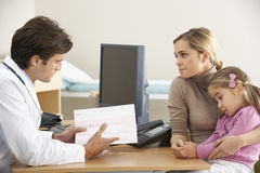 Doctor talking to mother and child Royalty Free Stock Images