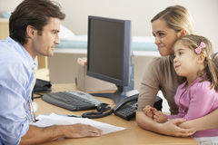 Doctor talking to mother and child Stock Photos