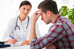 Doctor talking to patient. Doctor talking to her male patient at office Royalty Free Stock Photos