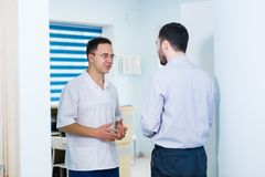 Doctor talking to a patient in a hallway.  Stock Image