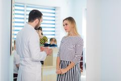 Doctor talking to a patient in a hallway.  stock photo