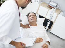 Doctor talking to patient in hospital bed Royalty Free Stock Photo