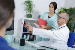 Doctor talking to patient nurse assistant aside Royalty Free Stock Image