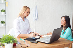 Doctor talking to patient in office, taking notes. Royalty Free Stock Photo