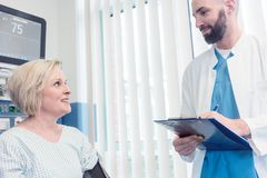 Doctor talking to patient in recovery room of hospital. After awaking from treatment or surgery Royalty Free Stock Image