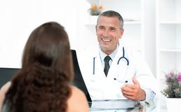 Doctor talking to patient sitting at the table Stock Images