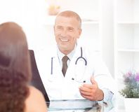 Doctor talking to patient sitting at the table. The concept of health Stock Images