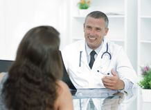 Doctor talking to patient sitting at the table. The concept of health Royalty Free Stock Photo