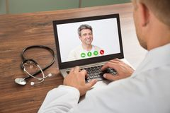Doctor talking to patient through video chat Stock Image