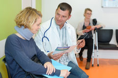 Doctor talking to patient wearing cervical-collar. Doctor talking to a patient wearing a cervical-collar stock images