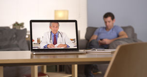 Doctor talking to patient who is texting on his smartphone. Doctor talking to patient who is on his smartphone Stock Images