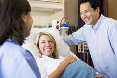 Doctor Talking To Pregnant Woman And Her Husband. In Hospital Ward stock photo