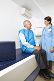 Doctor talking to senior before bone density measurement Royalty Free Stock Photography