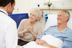 Doctor Talking To Senior Couple By Hospital Bed Royalty Free Stock Photography