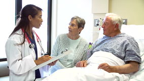 Doctor Talking To Senior Couple In Hospital Room stock footage