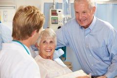 Doctor Talking To Senior Couple On Ward Stock Photo