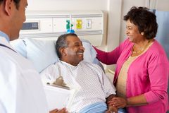 Doctor Talking To Senior Couple On Ward Stock Photos