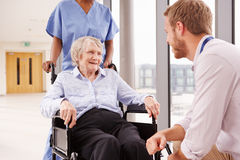 Doctor Talking To Senior Female Patient In Wheelchair Royalty Free Stock Photos