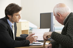 Doctor talking to senior male patient Stock Photo