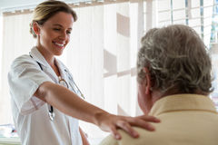 Doctor talking to senior man in retirement home royalty free stock photos
