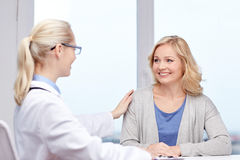 Doctor talking to woman patient at hospital. Medicine, health care, meeting and people concept - smiling doctor talking to women patient at hospital royalty free stock photography
