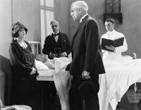 Doctor talking to a young woman in the hospital room of a sick patient. (All persons depicted are no longer living and no estate exists. Supplier grants that Stock Images