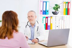 Doctor is talking with woman patient and sitting in medical office.Man in white uniform. Medical insurance. Copy space royalty free stock photography