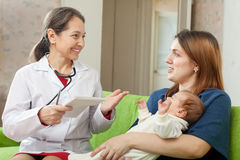 Doctor talks with mother of newborn baby. Friendly mature pediatrician doctor talks with mother of newborn baby Stock Image
