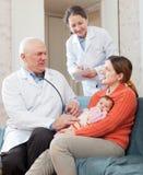 Doctor talks with mother of newborn baby. Nurse writes testimony Royalty Free Stock Image