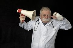 Doctor with tape across his mouth and listening to a message through a megaphone royalty free stock images
