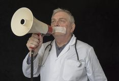 Doctor with tape across his mouth trying to shout into a megaphone royalty free stock image