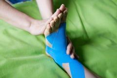 Doctor taping woman injury leg. Royalty Free Stock Photos